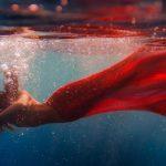 Donna oppressa danza in acqua con un vestito rosso